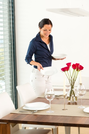 Pretty woman setting table dining room preparing plates Stock Photo - 17388973