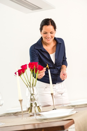 Smiling wife lighting candle romance flowers love Valentine's day Stock Photo - 17388956