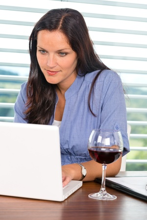 Young businesswoman relaxing home wine surfing internet laptop photo