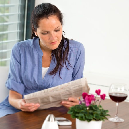 Woman reading newspaper relaxing drinking wine living room Stock Photo - 17388988