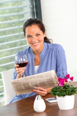 houseplant: Cheerful woman reading drinking wine newspaper living room