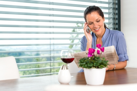 Smiling woman talking mobile phone relaxing reading home living room Stock Photo - 17388960
