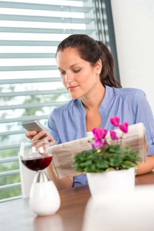 Young woman texting reading newspaper cell phone living room Stock Photo - 17388970