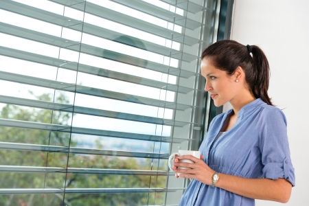 Young woman day dreaming looking window blinds drinking tea Standard-Bild