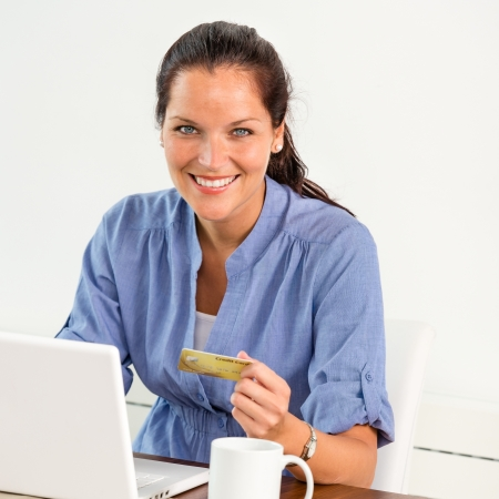 consumerism: Smiling woman paying bills online banking home credit card consumerism