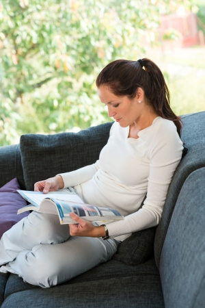 Young woman reading magazine living room couch sofa Stock Photo - 17388899