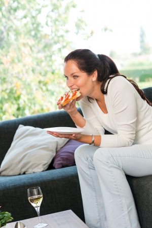 Woman eating sandwich lunch breakfast home sofa couch white wine Stock Photo - 17388915