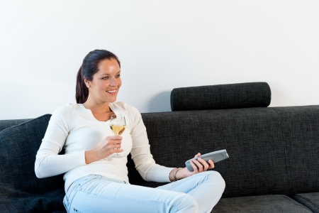 Happy woman lying down couch watching TV drinking wine Stock Photo - 17388887