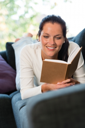 bookworm: Female student studying couch home bookworm woman living room Stock Photo