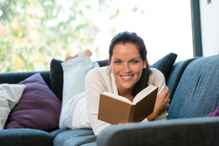Smiling woman resting reading sofa learning leisure activity Stock Photo - 17388974