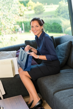 Young smiling woman sitting shopping bags couch shopaholic present Stock Photo - 17388906