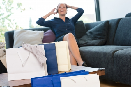 Cheerful woman talking phone shopping bags shopaholic couch living room Stock Photo - 17388965
