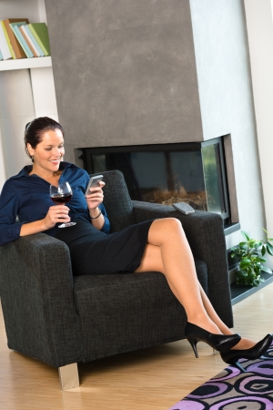 Happy woman relaxing armchair text messaging wine home inter businesswoman Stock Photo - 17388882