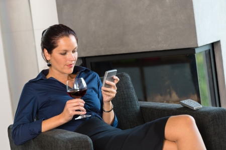 Woman businesswoman texting sms mobile phone living room drinking wine Stock Photo - 17388926