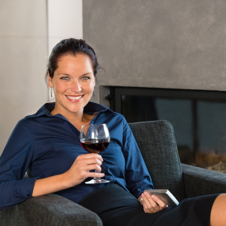 Young businesswoman resting work mobile phone drinking wine living room Stock Photo - 17388955
