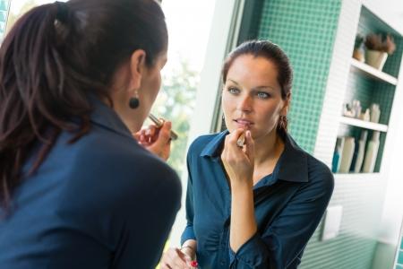 Young woman applying lipstick make-up beauty bathroom cosmetics mirror Stock Photo - 17388950