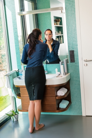 applying lipstick: Elegance woman using lipstick bathroom barefoot beauty make-up cosmetics