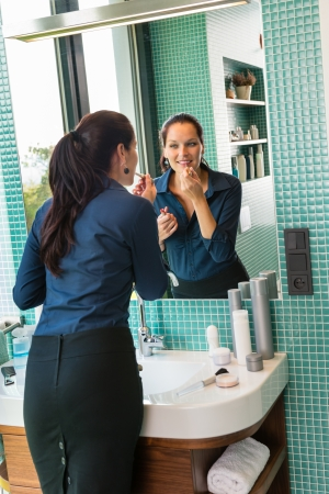 Smiling woman bathroom applying lipstick cosmetics businesswoman hygiene mirror photo
