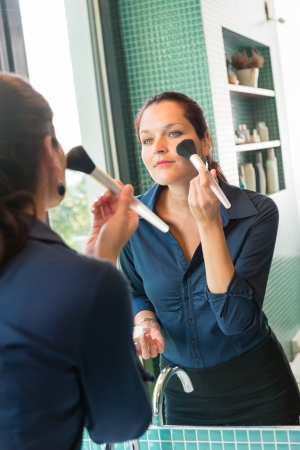 Young woman applying face powder bathroom brush mirror cosmetics elegance Stock Photo - 17388954