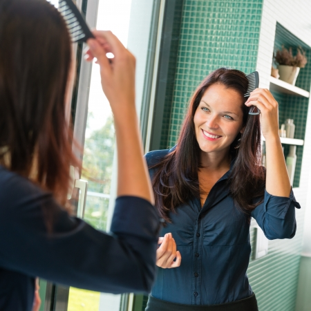 Young woman combing hair comb mirror bathroom morning preparation Stock Photo - 17388963