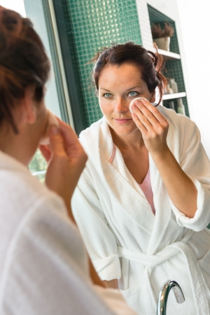 cotton pad: Young woman cleaning face cotton pads bathrobe bathroom morning preparation Stock Photo