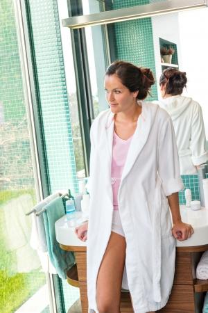 Woman leaning basin bathrobe bathroom thinking morning reflection spa treatment photo