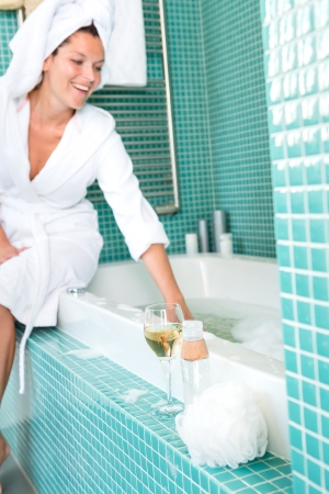 Smiling woman relaxing wrapped towel bathroom bathtub playing foam photo