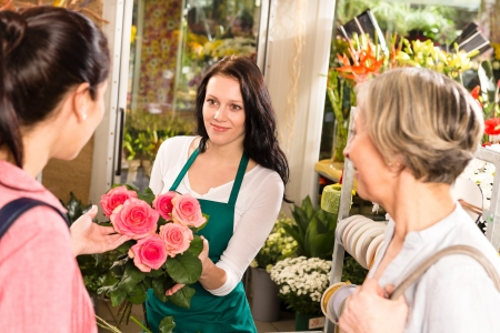 Happy young florist woman showing roses flowers customers shop Stock Photo - 17692545