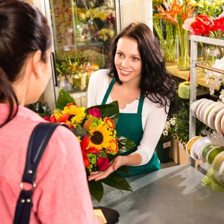 shop assistant: colorful bouquet florist woman selling customer flower shop store Stock Photo