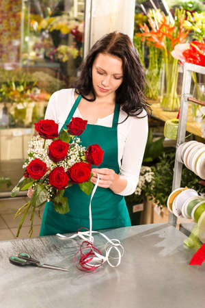 Woman florist working flowers roses market making bouquet store photo
