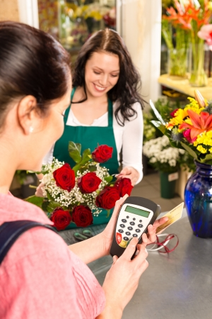 Woman florist selling flowers customer paying credit card red roses photo