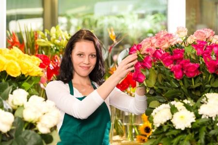 Jeune femme heureuse arranger les fleurs roses colorées boutique de fleuriste Banque d'images