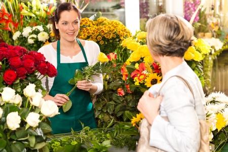 Young woman arranging flowers shop market selling customer smiling Standard-Bild