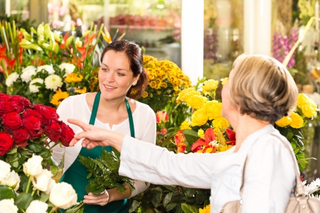 florists: Senior customer buying red roses flower shop florist women working