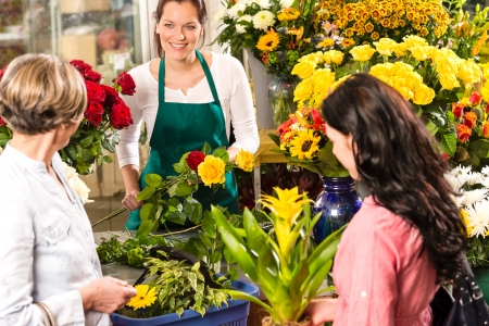 Florist woman preparing bouquet customers flower shop market happy photo