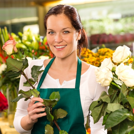 florists: Smiling florist cutting rose flower shop young woman