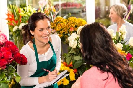 Happy florist writing flower shop talking customer woman Standard-Bild