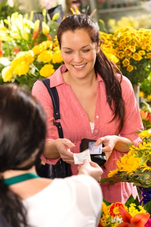 Woman customer taking receipt flower shop buying credit card photo