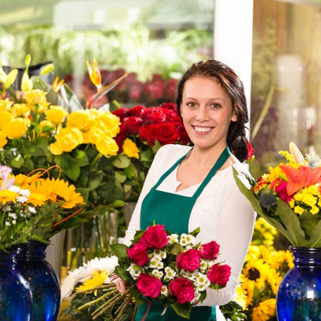 Cheerful female florist bouquet roses flower shop posing owner photo