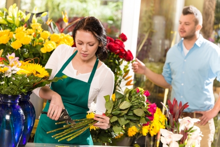 Woman florist cutting flowers shop bouquet man customer choosing