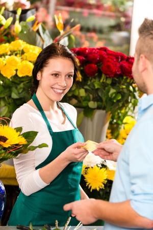 Smiling florist man customer buying flowers credit card shop photo