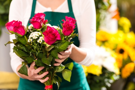 Florist hands showing red roses bouquet flowers shop market photo
