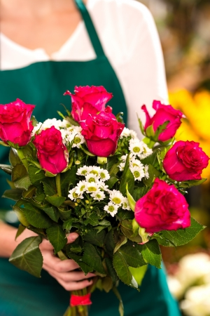 Florist woman holding red roses bouquet hands flower shop photo