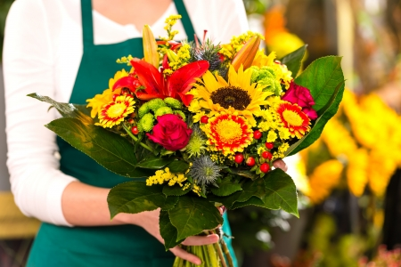 Florist holding bouquet colorful flowers shop assistant hands photo
