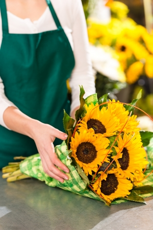 Florist preparing sunflowers bouquet flower shop assistant yellow hands photo