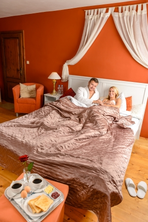 Smiling man woman hotel room relaxing breakfast lying bed Stock Photo - 17887240