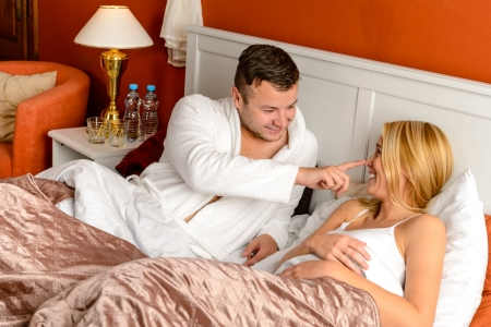Young man stroking woman lying bed happy couple motel room Stock Photo - 17887266