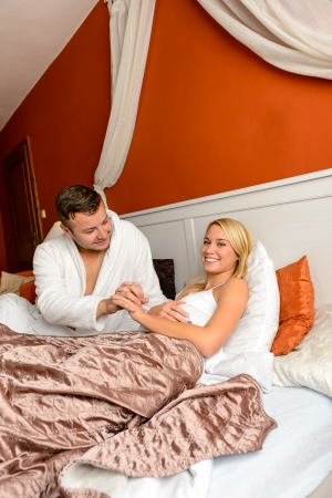 Cheerful loving couple holding hands lying bed room romantic Stock Photo - 17887246