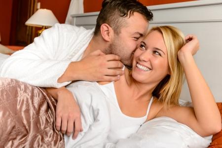 enamorados besandose: Pareja feliz en la cama del hombre que da beso la mejilla de la mujer Foto de archivo
