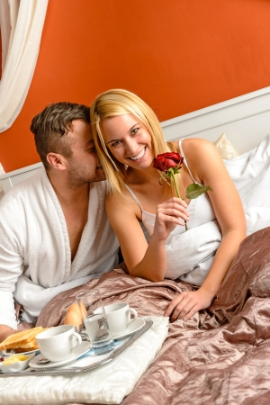 getaways: Cuddling couple cuddling bed motel room celebrating anniversary rose Stock Photo
